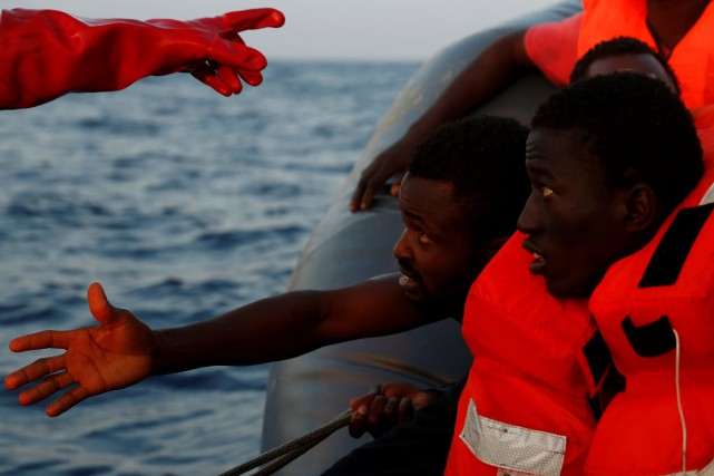 Migrants on board a rubber dinghy await rescue... (REUTERS)