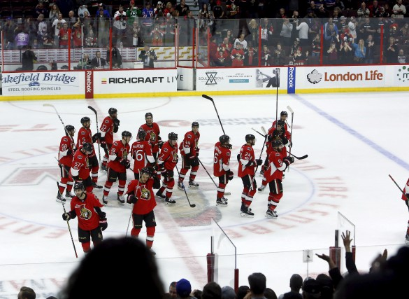 Ottawa Senators players raise their sticks in recognition... (THE CANADIAN PRESS)
