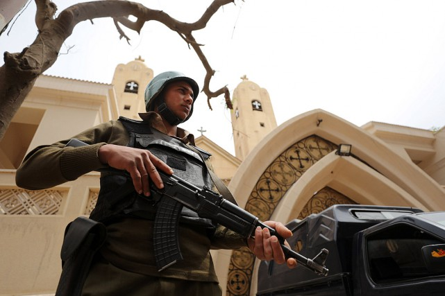 Un policier armé monte la garde devant l'église... (Photo Mohamed Abd El Ghany, archives REUTERS)