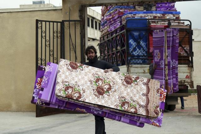 Un homme transporte des matelas en prévison de... (AFP, Mohamed al-Bakour)