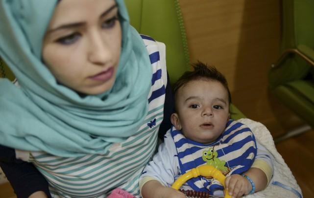Gufran Ali tient son fils de huit mois,... (AFP, Money SHARMA)