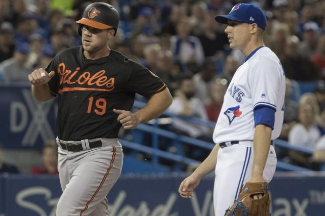 Chris Davis passe devant le lanceur Aaron Sanchez... (Photo Fred Thornhill, La Presse canadienne)