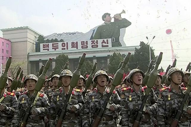 Des soldats défilent avec leurs armes.... (Image tirée d'une vidéo, AP)