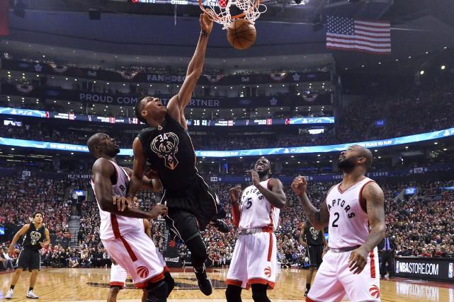 Giannis Antetokounmpo (34) réussi un dunk devant Serge... (Photo Nathan Denette, La Presse Canadienne)