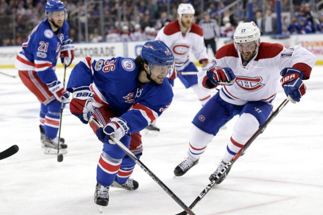 Mats Zuccarello est pourchassé par Torrey Mitchell.... (PHOTO Seth Wenig, Associated Press)