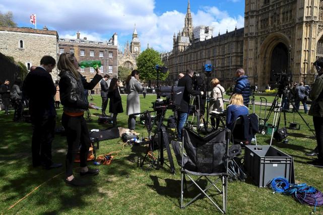 Des membres des médias s'assemblent sur le gazon... (AFP, Justin Tallis)