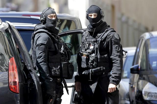 Des policiers cagoulés patrouillent dans les rues de... (AP, Claude Paris)