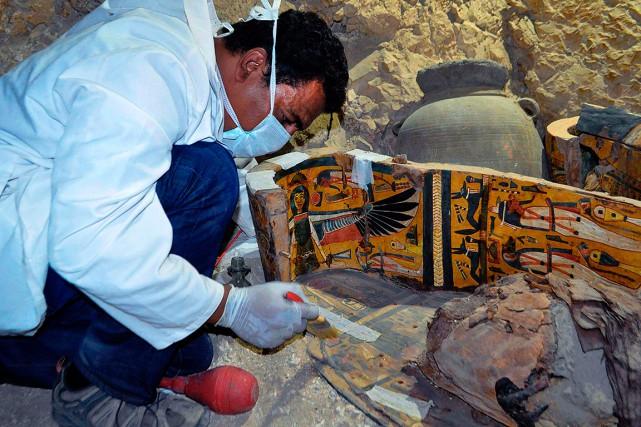 Dans la tombe, des experts égyptiens s'activent autour... (STRINGER, AFP)
