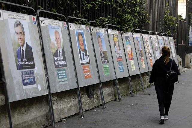 Une femme marche devant une série d'affiches des... (Photo Ludovic MARIN, AGENCE FRANCE-PRESSE)