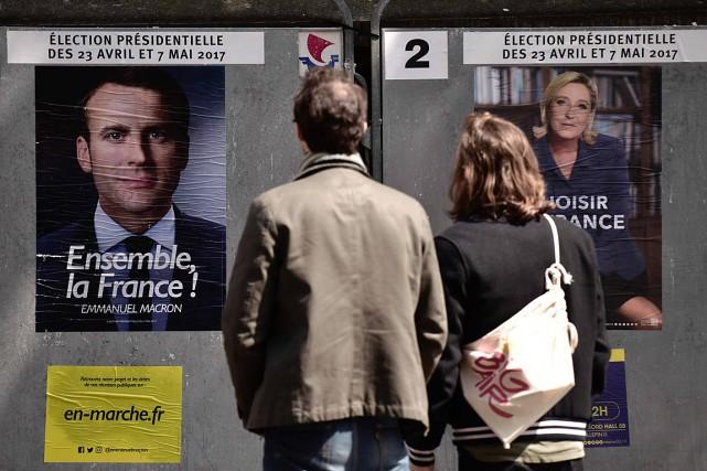 Un homme et une femme regardent des affiches... (Photo Philippe LOPEZ, AGENCE FRANCE-PRESSE)