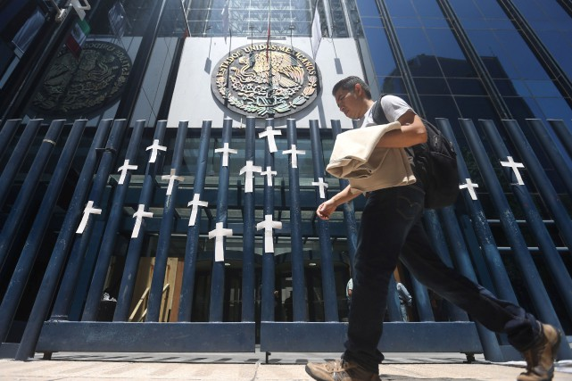 Un homme passe devant des croix rendant hommage... (PHOTO ARCHIVES REUTERS)