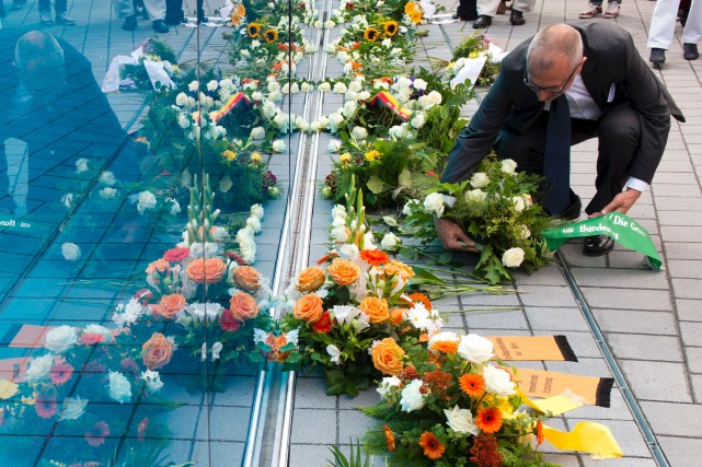 Un visiteur dépose des fleurs devant le Mémorial... (AFP, John MacDougall)