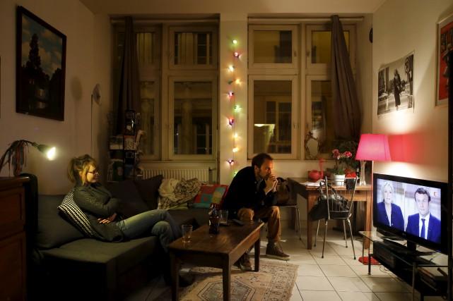 Un couple regarde le débat à Lyon.... (AP, Laurent Cipriani)