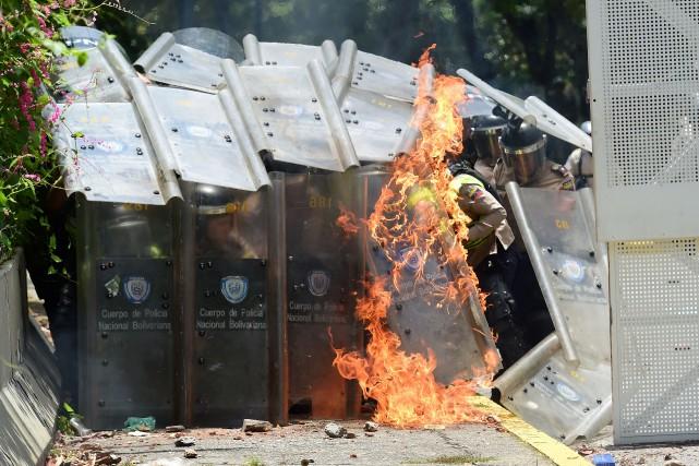 Un cocktail Molotov explose sur le bouclier d'un... (PHOTO RONALDO SCHEMIDT, AFP)