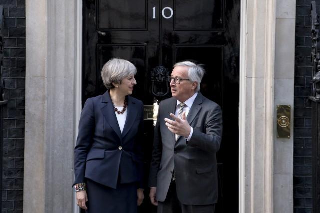 Theresa May et Jean-Claude Juncker devant le 10,... (AFP, Justin Tallis)