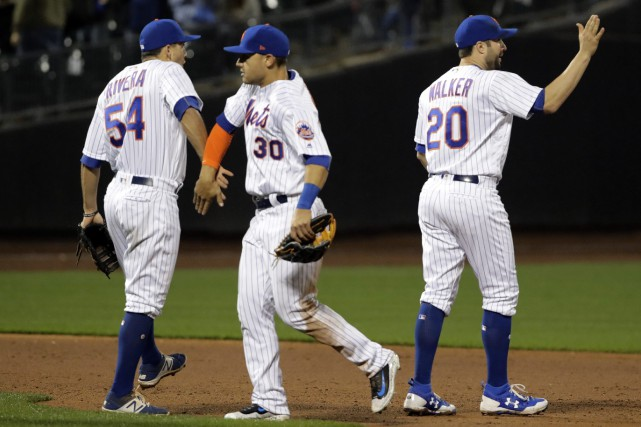 Michael Conforto (30), T.J. Rivera (54) et Neil... (Photo Frank Franklin II, AP)
