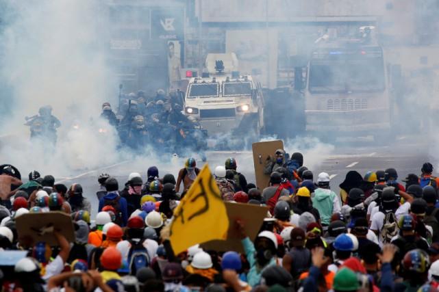 Brandissant des drapeaux vénézuéliens et des pancartes sur... (PHOTO REUTERS)