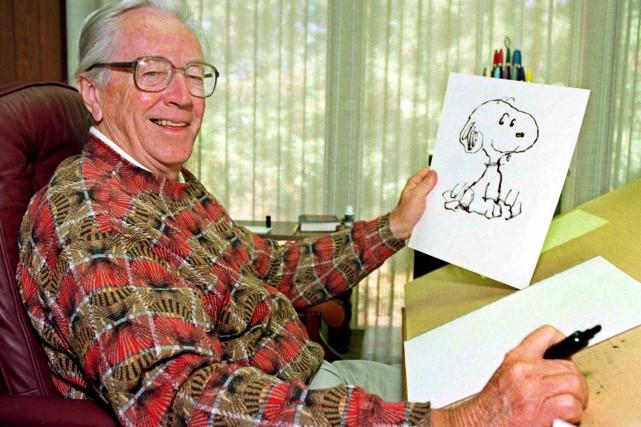 Le bédéiste Charles Schulz montre un dessin de... (Associated Press, Ben Margot)