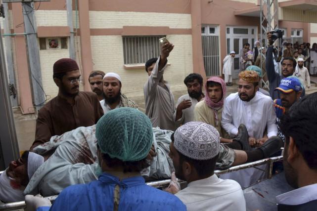 Des volontaires transportent une victime de l'explosion survenue... (AFP, BANARAS KHAN)