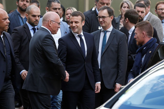 Emmanuel Macron (au centre) distribue des poignées de... (PHOTO CHARLY TRIBALLEAU, AGENCE FRANCE-PRESSE)