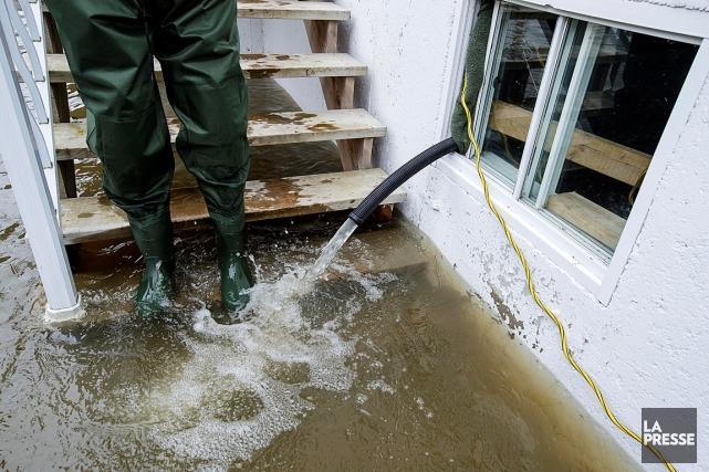 De l'eau provenant d'un sous-sol inondé s'écoule par... (PHOTO ALAIN ROBERGE, ARCHIVES LA PRESSE)