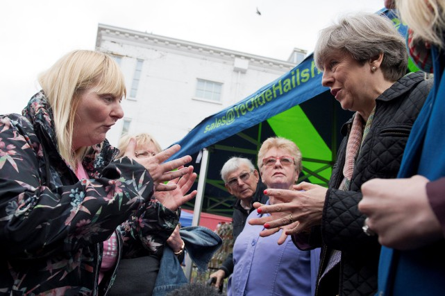 Theresa May (à droite) discute avec une dame... (Photo Justin Tallis, REUTERS)