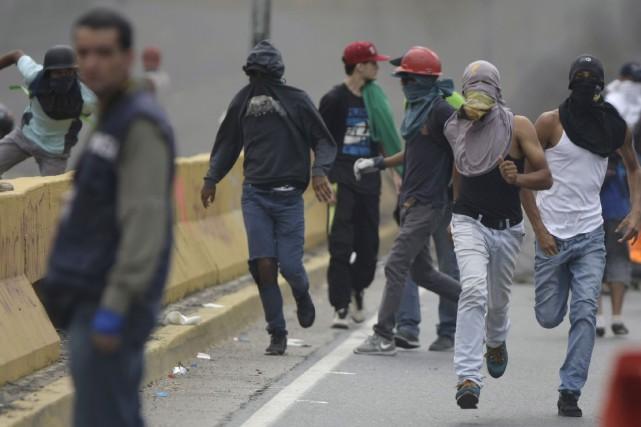 Des groupes de manifestants cagoulés ont disposé des... (AP, Fernando Llano)