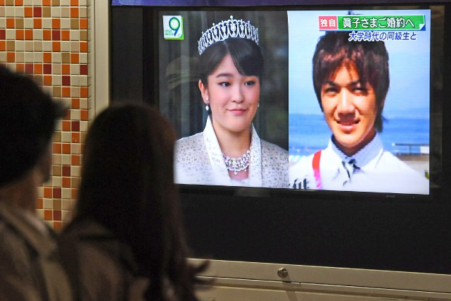 Des passants devant les photos à la télévision... (Photo Hitoshi Takano, Kyodo News via AP)