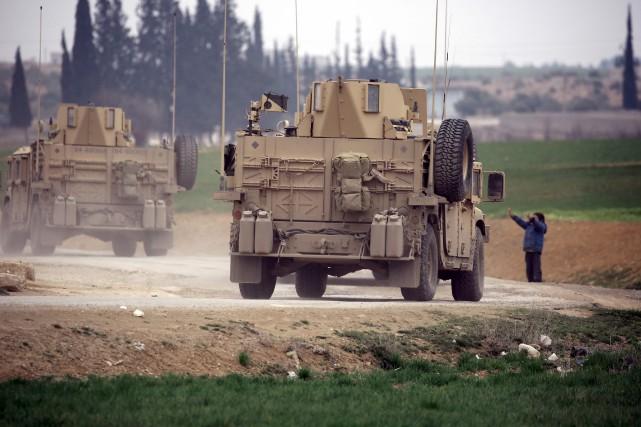 Un enfant salue des véhicules militaires américains, dans... (PHOTO AFP)
