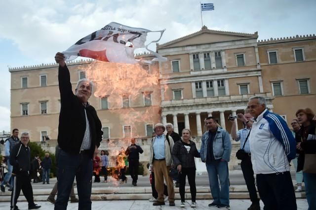 Un homme brûle un drapeau du parti au... (PHOTO AFP)