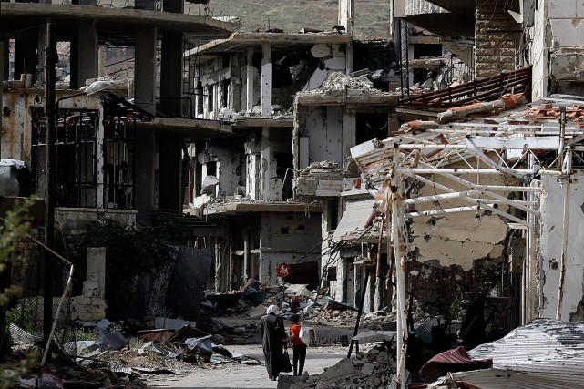 Des résidants marchent dans une rue de Zabadani,... (PHOTO AP)