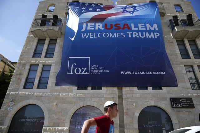 Un jeune homme passe devant une affiche souhaitant... (PHOTO AHMAD GHARABLI, AGENCE FRANCE-PRESSE)