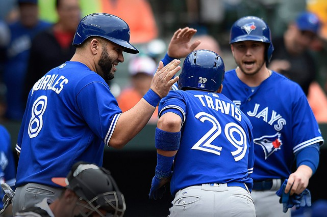 Devon Travis est félicité par Kendrys Morales et... (PHOTO Gail Burton, ASSOCIATED PRESS)