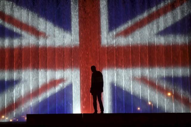 Un homme se tient devant une fontaine illuminée... (AFP)