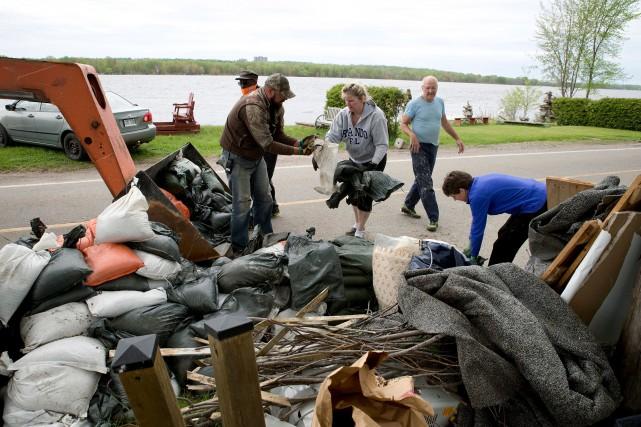 Des bénévoles qui retirent des sacs de sable... (Martin Roy, Le Droit)