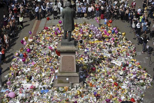 Fleurs et messages s'accumulent à la place St... (AFP, Oli Scarff)