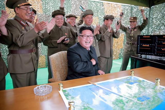 Kim Jong Un, au centre, réagit au lancement... (KCNA via REUTERS)