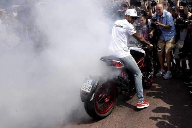 Lewis Hamilton, qui a amusé vendredi la foule... (AP, Claude Paris)