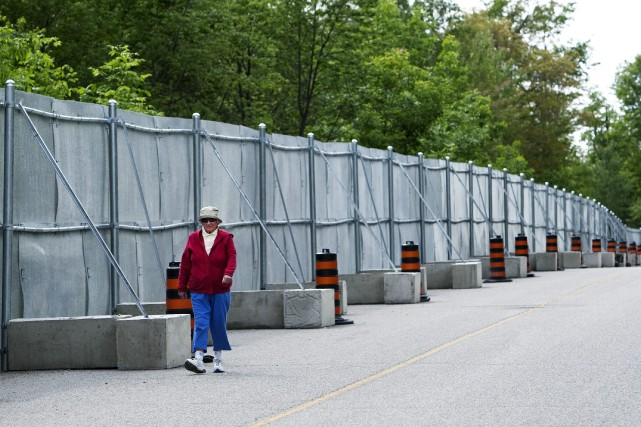 Une femme marche le long des barrières de... (PHOTO: NATHAN DENETTE, PC)