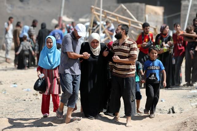 Des Irakiens évacuent le quartier de Zanjili, dans... (Photo Karim Sahib, Agence France-Presse)