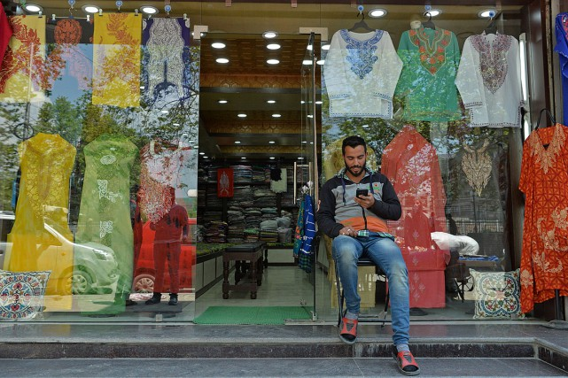 Un homme regarde son téléphone devant son magasin... (PHOTO TAUSEEF MUSTAFA, ARCHIVES AGENCE FRANCE-PRESSE)