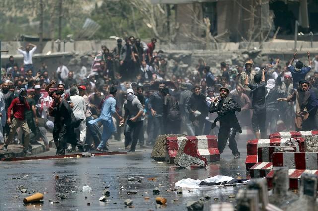 Les manifestants rassemblés près du site de l'explosion... (PHOTO MASSOUD HOSSAINI, ASSOCIATED PRESS)
