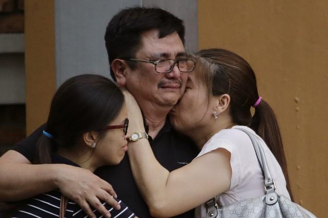 Un homme tente de consoler les membres de... (Photo Aaron Favila, Associated Press)