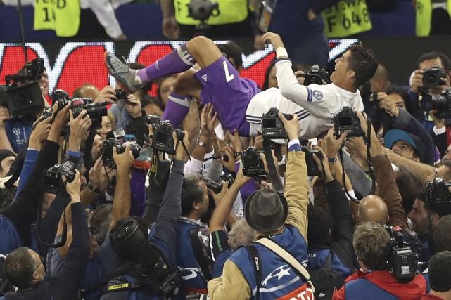 Cristiano Ronaldo est porté en triomphe par ses... (AP, Alastair Grant)