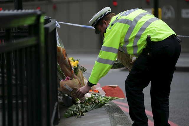 Un policier dépose des fleurs du côté nord... (AFP, Daniel Leal-Olivas)