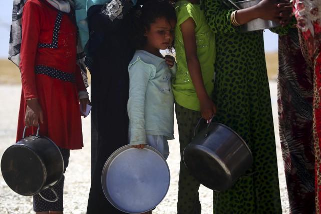 Des civils syriens font la queue pour recevoir... (AFP, Delil Souleiman)