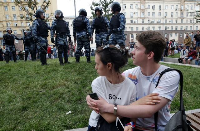 Un couple de manifestants observe des policiers anti-émeutesur... (PHOTO REUTERS)