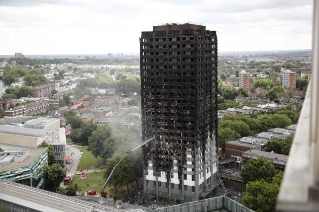 Un lance d'incendie automatisée continue d'arroser la tour... (AFP, Tolga AKMEN)