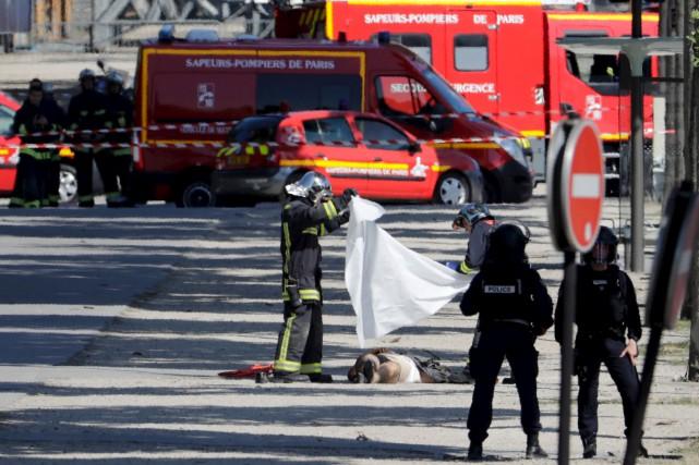 Des secouristes recouvrent le corps de l'assaillant dans... (AFP, Thomas Samson)
