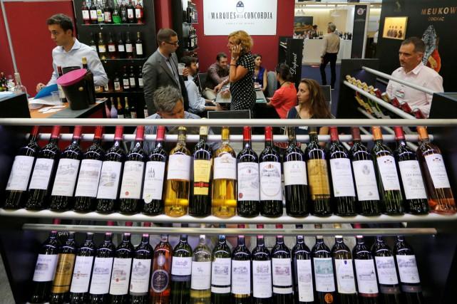Des gens dégustent des vins à Vinexpo.... (PHOTO AFP)